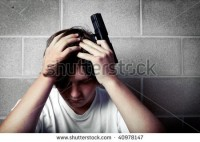stock-photo-teen-depression-teenager-with-hands-on-head-holding-handgun-40978147