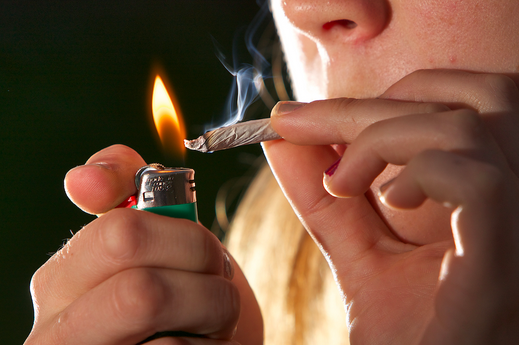 This is a picture of an adolescent burning marijuana wrapped in paper and smoking this, the structure being used to smoking is called a joint.