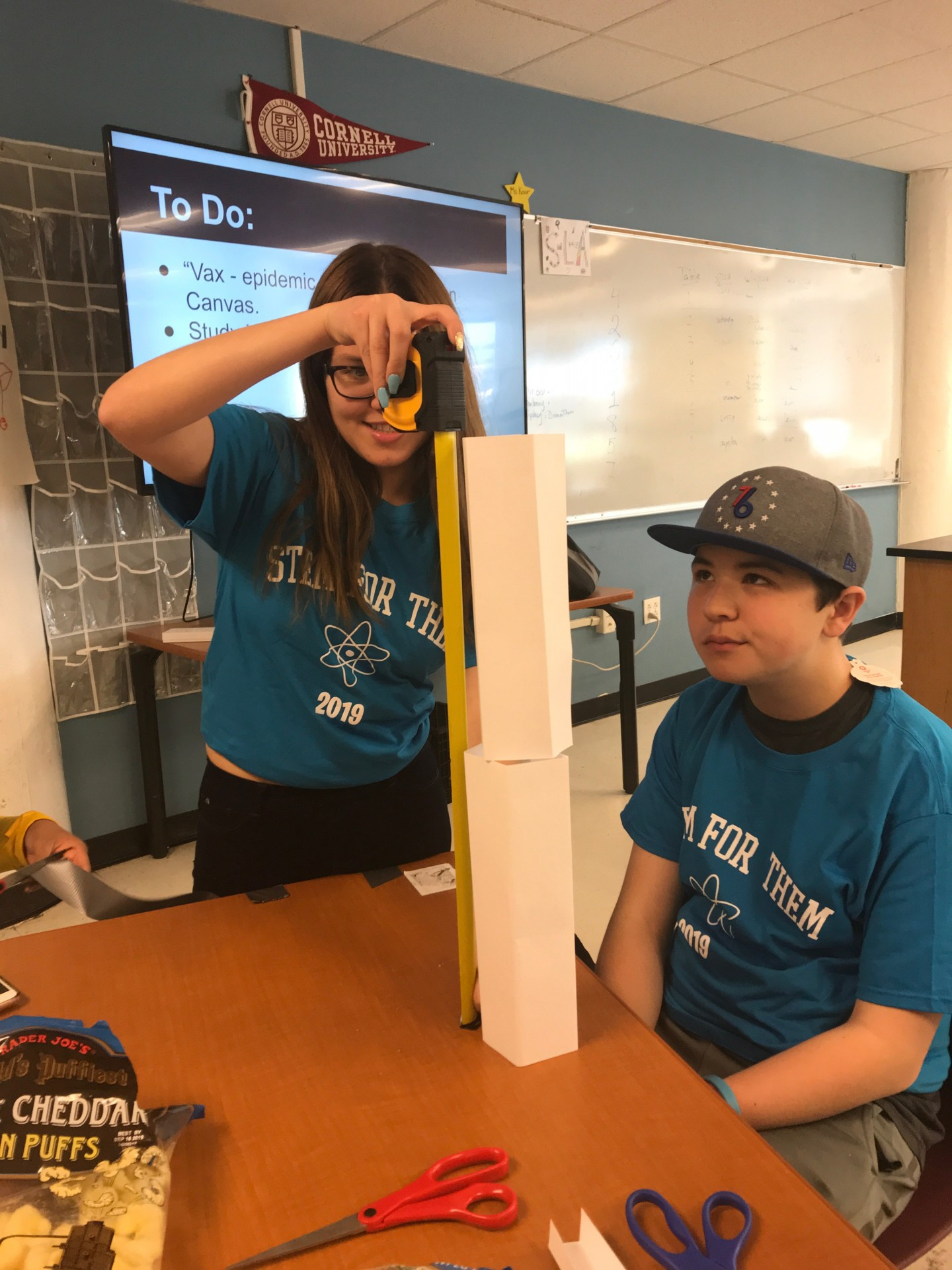 Measuring the length of Max's paper tower after completing the NCOTI inspired activity.