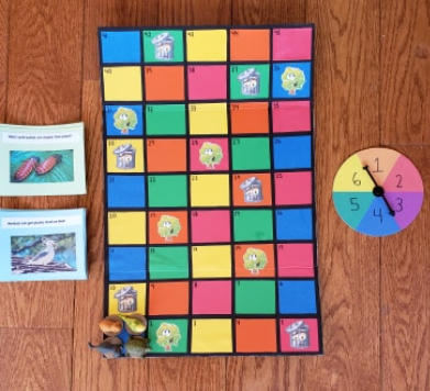 The board game and on the side are two stacks of cards. One pile corresponds with the pictures of trees, with fun facts debunking bad reputations of the animals and how they help the environment. The second pile of cards corresponds with the pictures of t