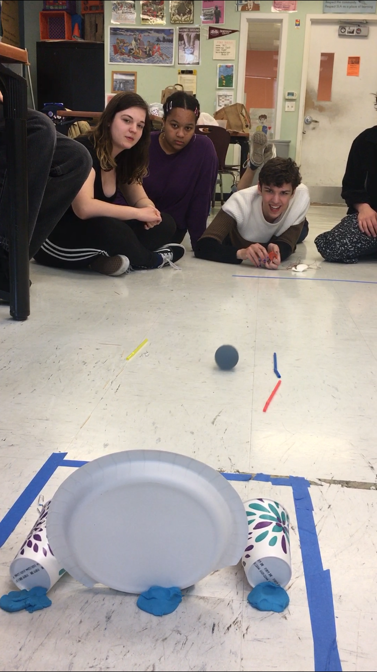Team 2 performing their solution to the same prompt with the same constraints, but with a totally different approach. They created a corral to trap the balls they rolled in the scoring area.